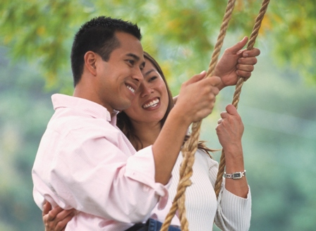 Young Asian couple sitting on swing