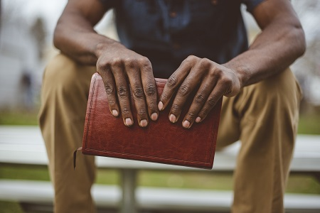 Closeup shot of a male sitting in the park while holding the bible with a blurred background